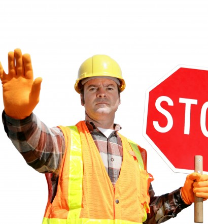 A construction worker stopping traffic, holding a stop sign.  Isolated on white.